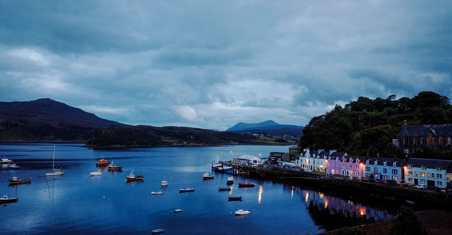 portree on the isle of skye in scotland  at sunset with calm loch and