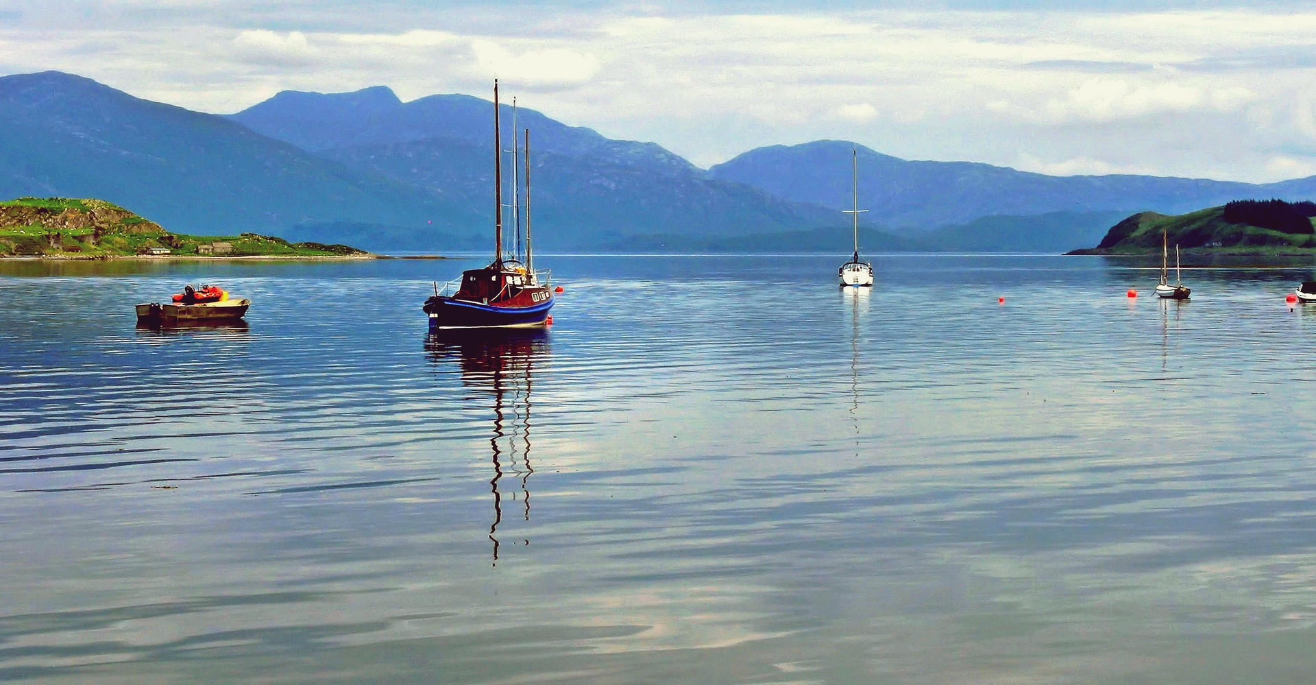 Sailing boats in loch near Oban with mountain scenery in scotland