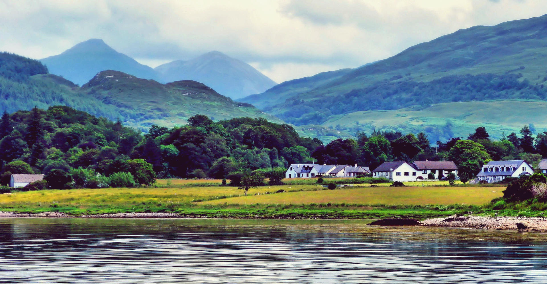Scenery near Oban scotland with loch beach and mountains green trees and clouds