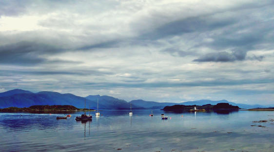 scenery near oban scotland with boats in calm loch and mountains and sky
