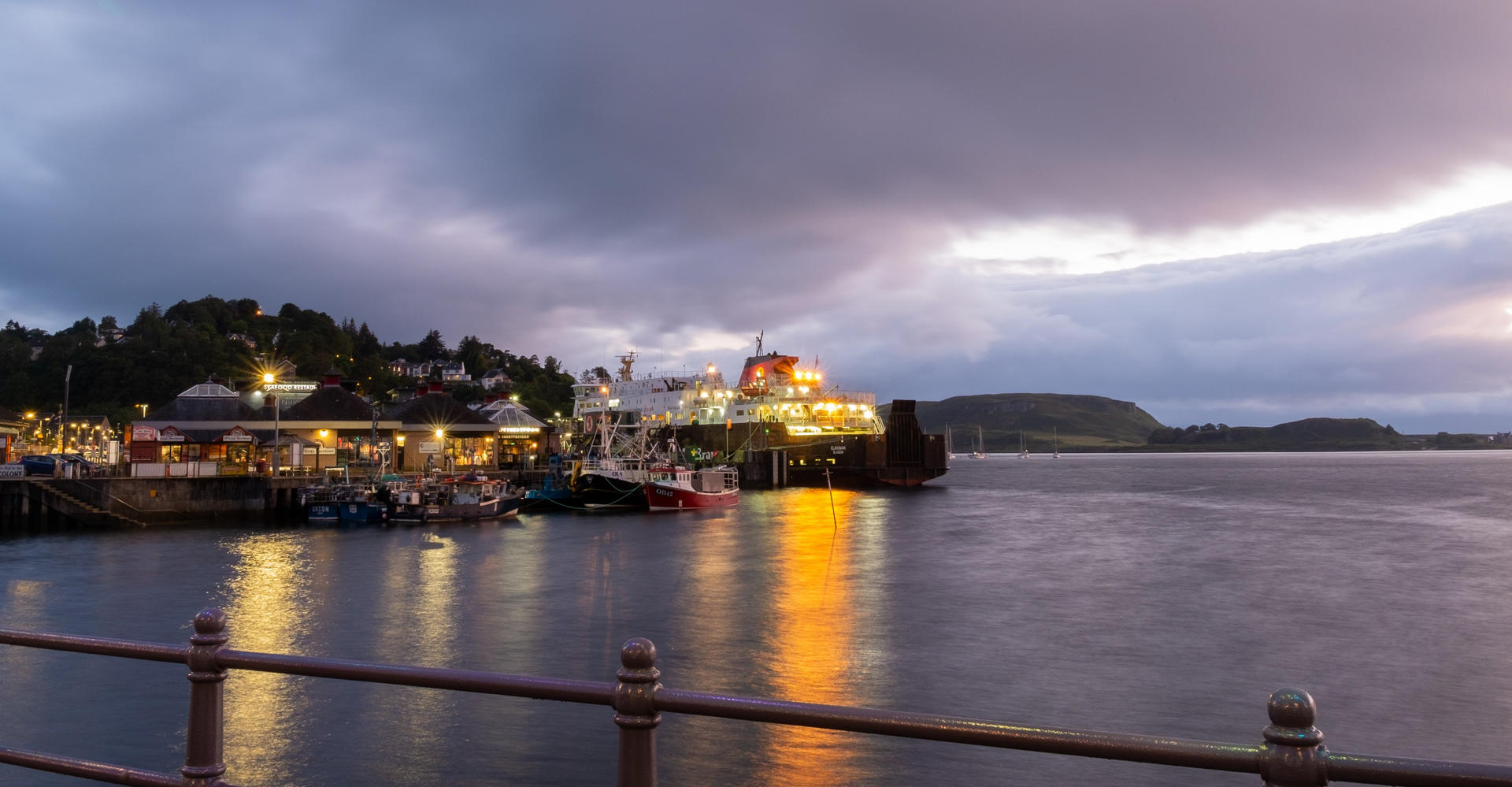 Evening in Oban harbour showing sea loch and ferry in scotland