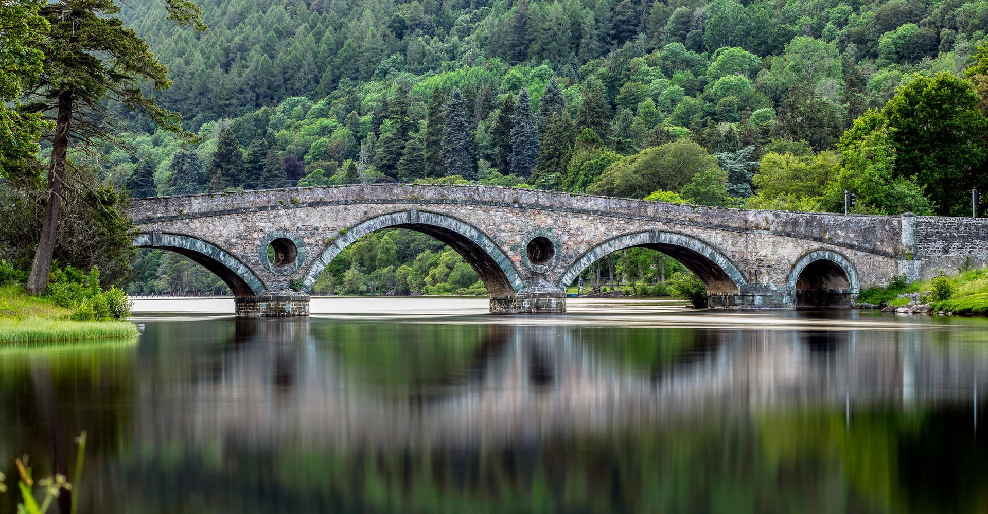 Stone Bridge over the River Tay in scotland with forest on hills in background