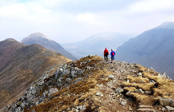 people on private tour in glencoe walking on hillside with mountains and skye