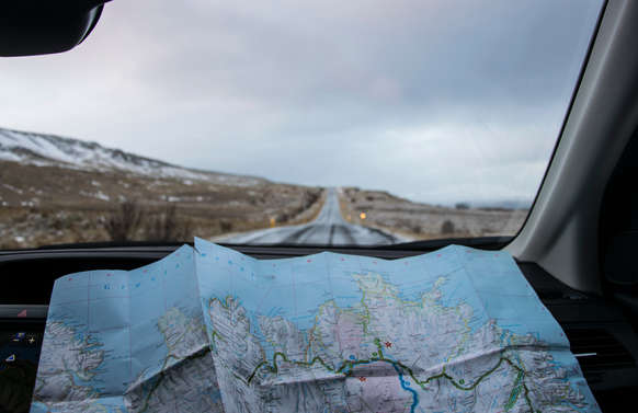 looking at map inside car with open road on luxury private tur