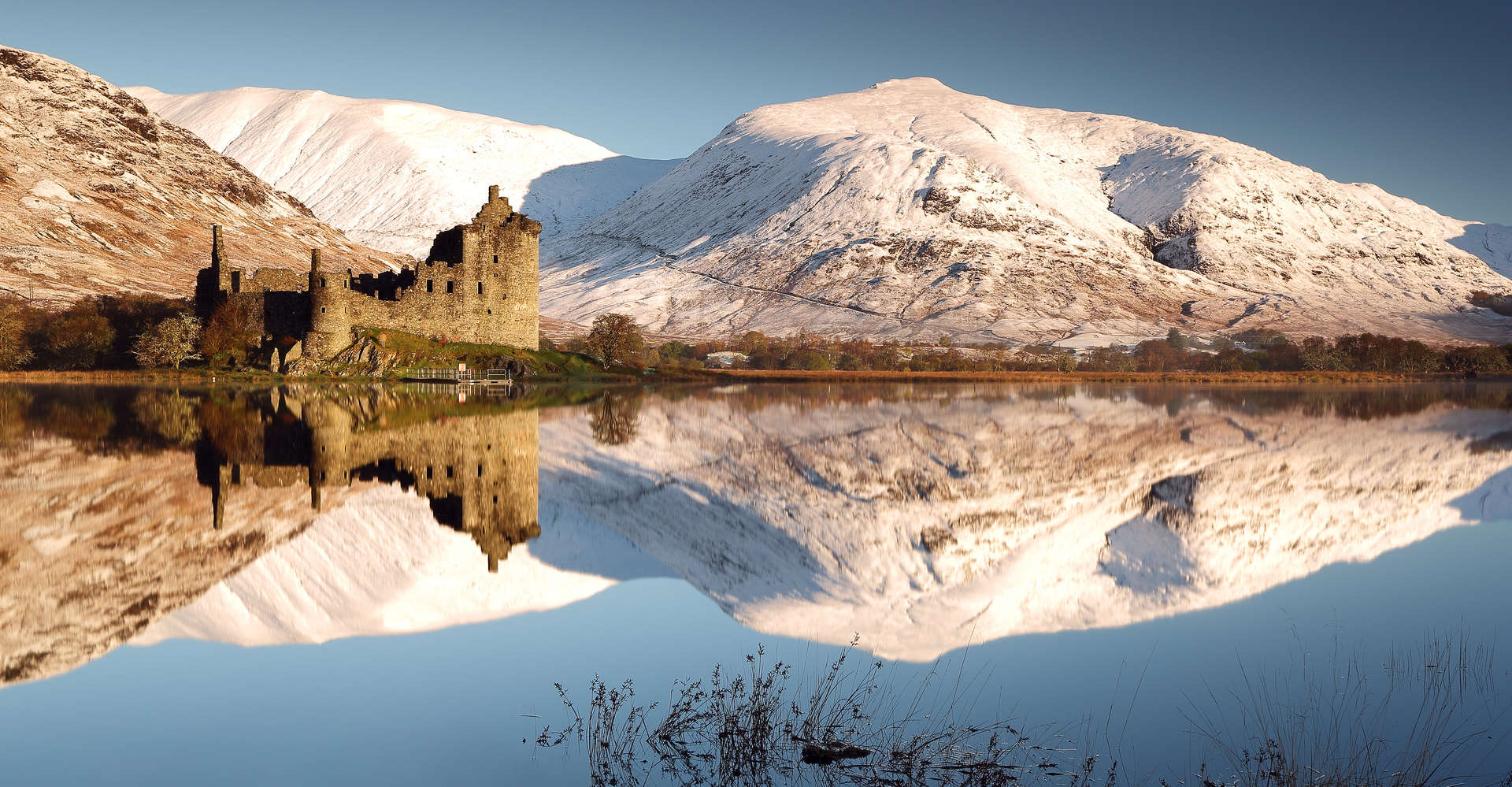 private tour to kichurn castle on loch awe in scotland with snowy mountains in background