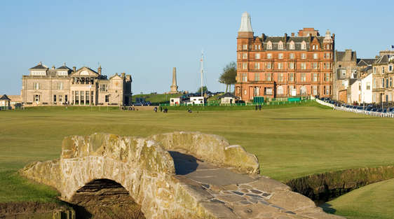 swilcan bridge in st andrews golf course scotland with hotel and blue sky
