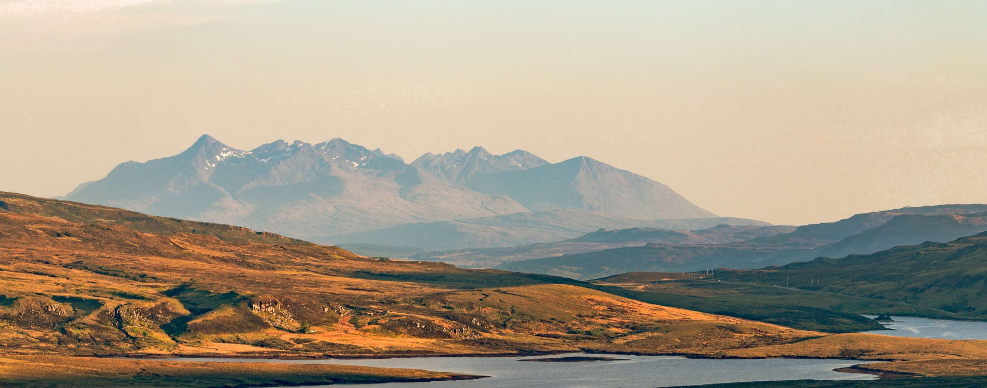 Cuillin Ridge, Isle of Skye, scotland seen from distance with clear red skye and river in foreground