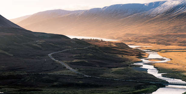 scenic road through mountains and hills in perthshire scotland with river mountains and sky