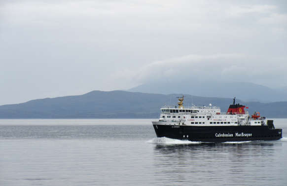 ferry sailing across loch in scotland with mountains and sky