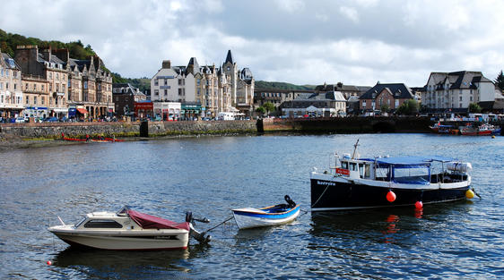 harbour sea with boats in oban scotland showing town buildings and sky