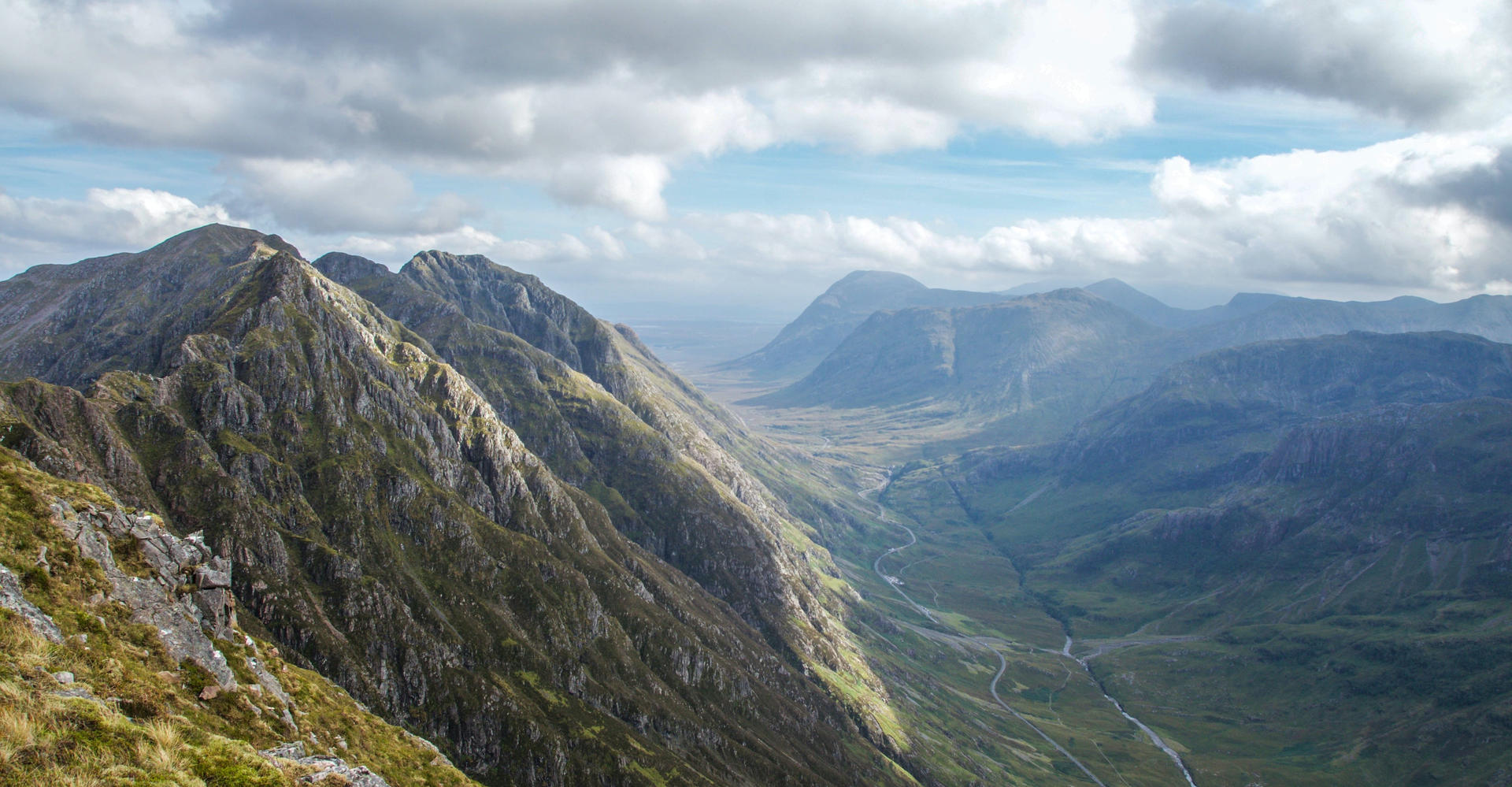 mountain landscape of glencoe scotland seen from high on peak with sunny sky and clouds