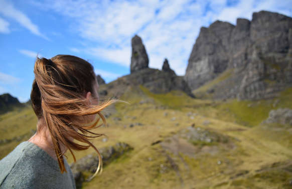 tourist on private tour looking at old man of storr in skye, scotland