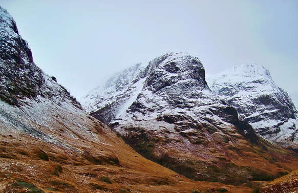 three sisters of glencoe with snow on the mountains