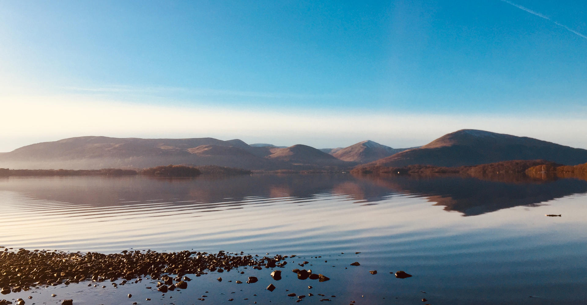Loch lomond in scotland from Millarochy Bay with calm loch and clear blue skye and ripples on still water