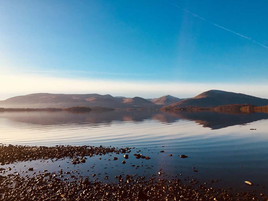 loch lomond in scotland seen from millarochy bay with blue sky and mountains