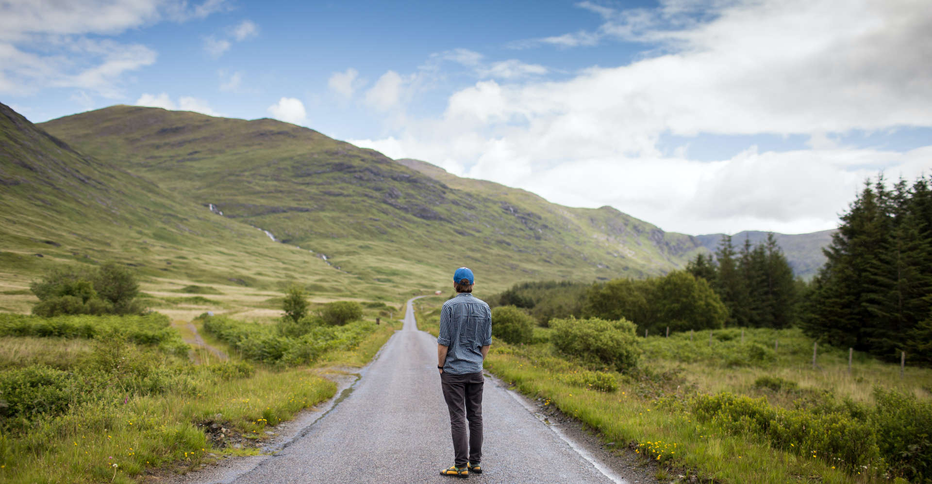 man on luxury private tour in scotland standing in middle of open road