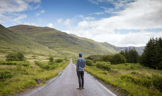 man on luxury private tour standing in middle of road in scotland