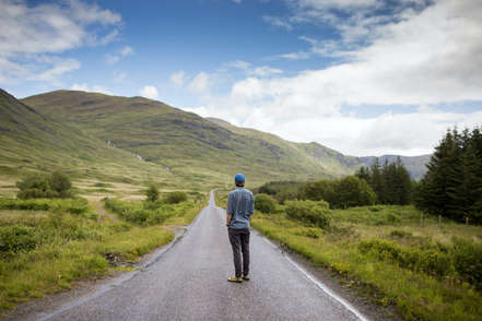 man on luxury private wildife tour in scotland standing in road