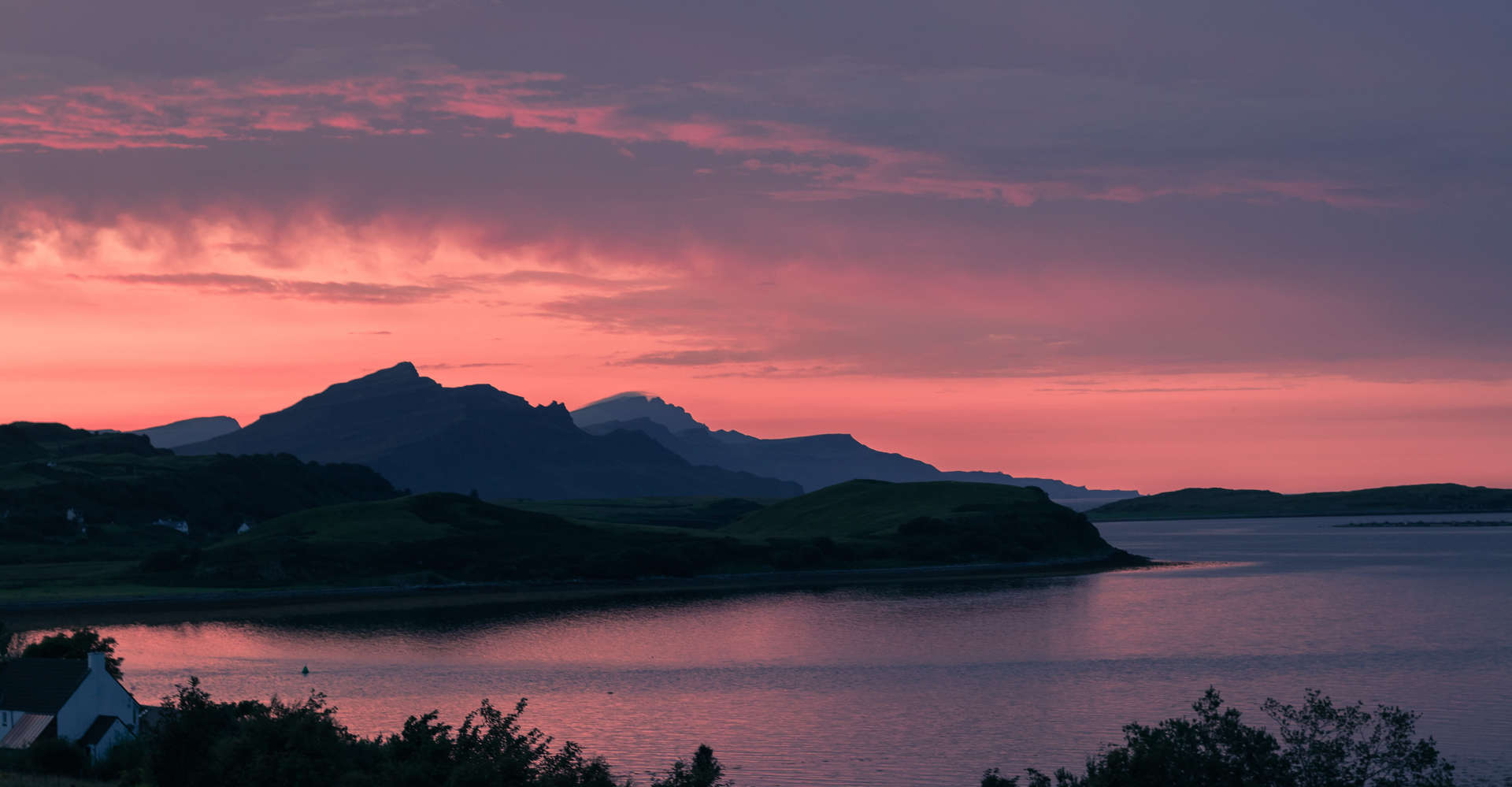 mountains of the isle of skye in scotland at sunset with red sky