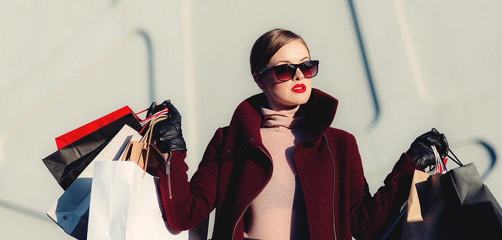 Woman in sunglasses with multiple shopping bags.