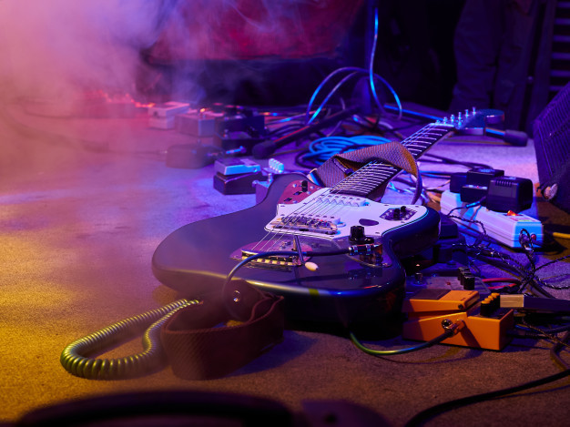 Electric guitar with cables, audio pedals on stage during a concert, Spinal Cordz