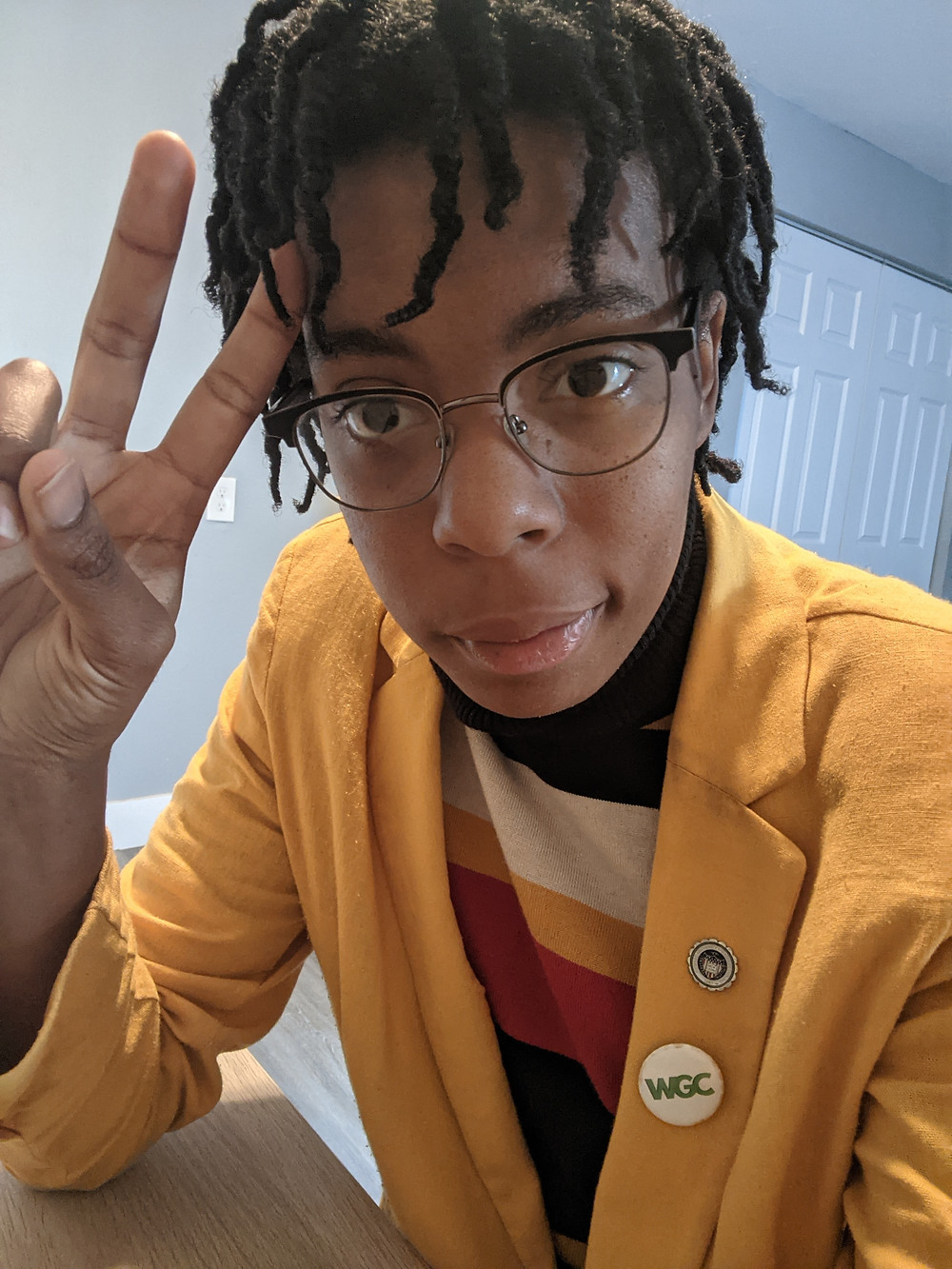 A photo of Jade Madison Scott in a yellow blazer and multi-colored turtleneck