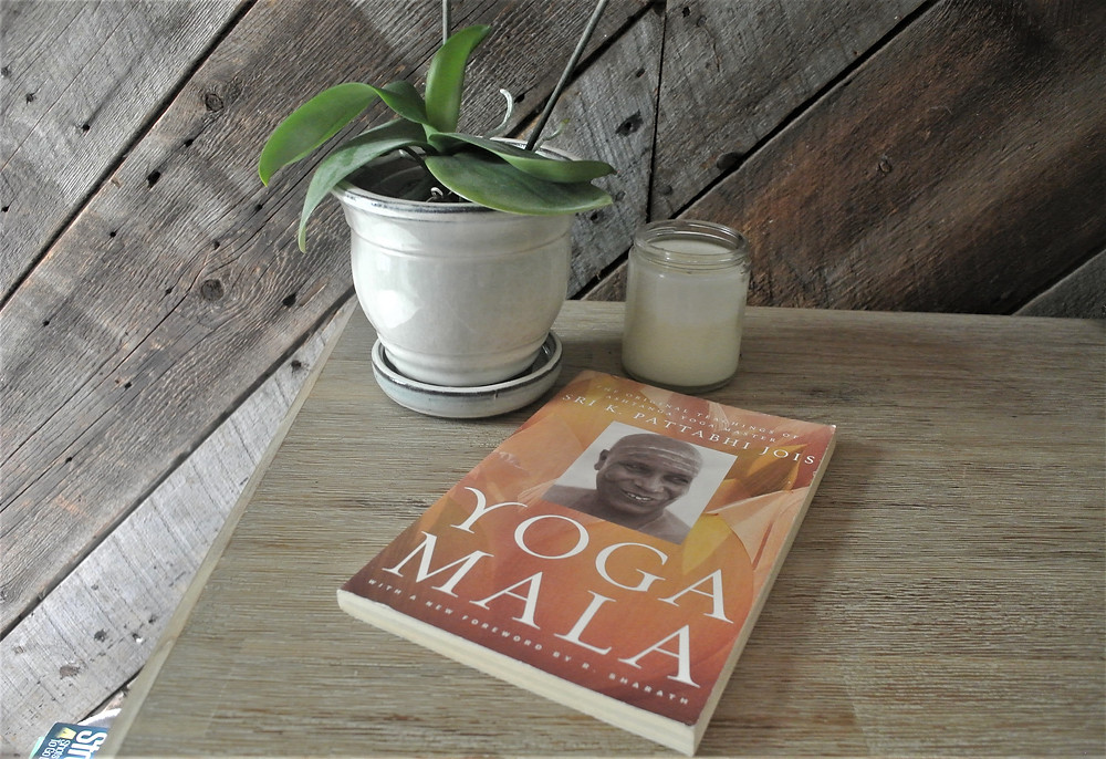 Potted plant with a candle and yoga mala book on a nightstand