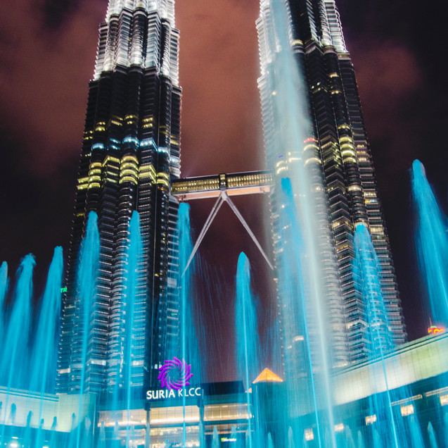 Petronas Towers and KLCC fountain show at night.