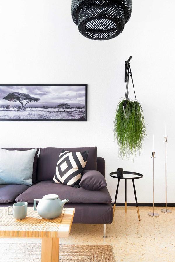 Salon décoré avec coussins, théière y chandeliers en métal de H&M Home