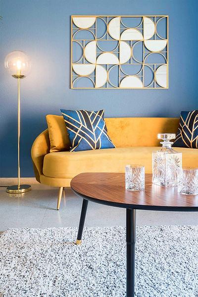 Salon decorado con un sofá vintage de terciopelo amarillo de Maisons du monde
