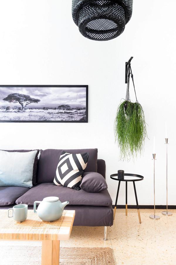 Sala d'estar decorada amb coixins, tetera i portaespelmes de metall d'H&M Home
