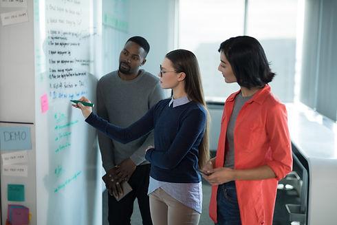 male-and-female-executives-writing-on-whiteboard-QXKTW36.jpg