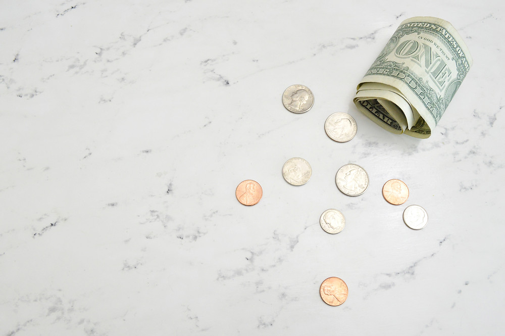 dollar bill and coins on a marble surface