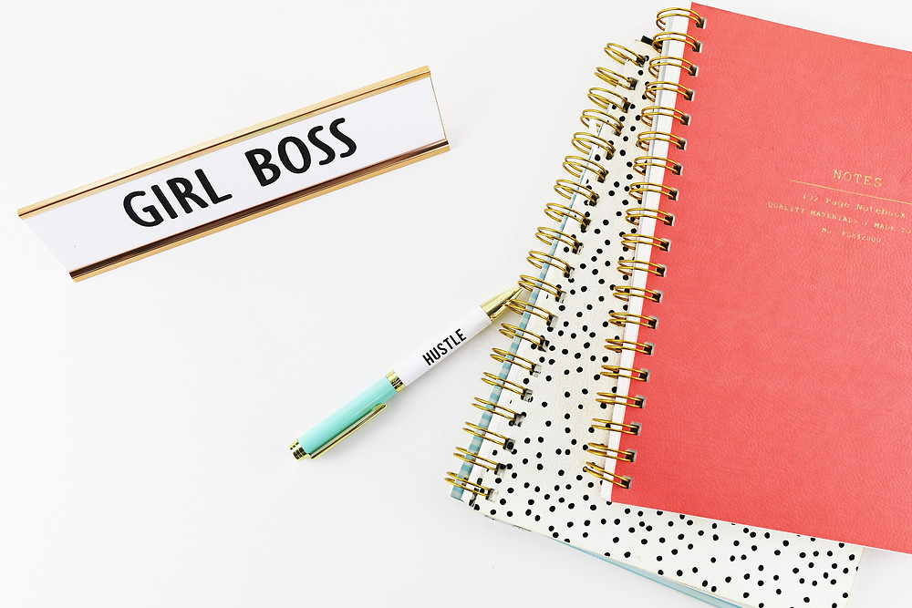 stack of notebooks with pen and a girl boss nameplate