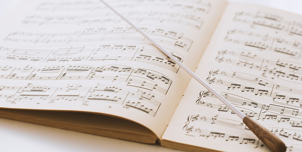 Conductor's baton on sheet music_edited.