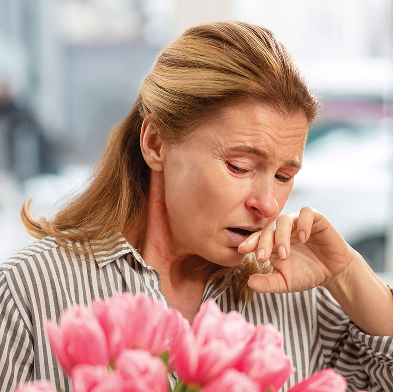 woman looking at flowers and sneezing from Spring allergies