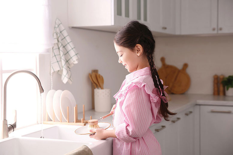 young woman dressed  in pink at the kitchen sink doing dishes