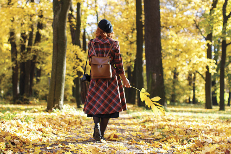 woman wearing a plaid coat and a beret walking through a forest of fall colors