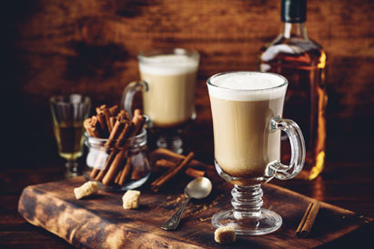 Mugs of Irish coffee with whiskey in the background