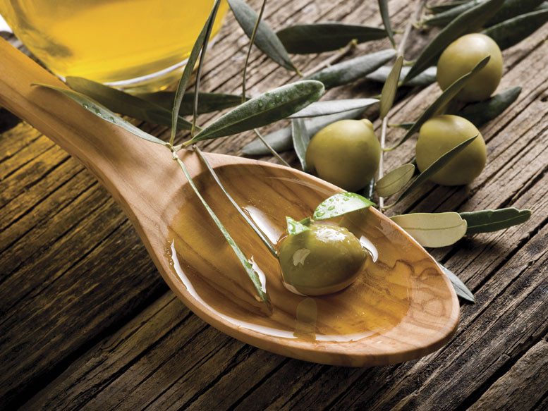 olive in a wooden spoon