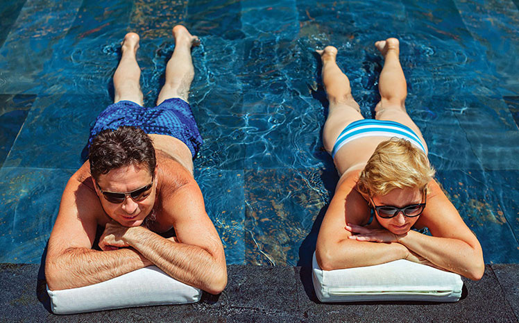 two people lying in the sun in water to stay cool