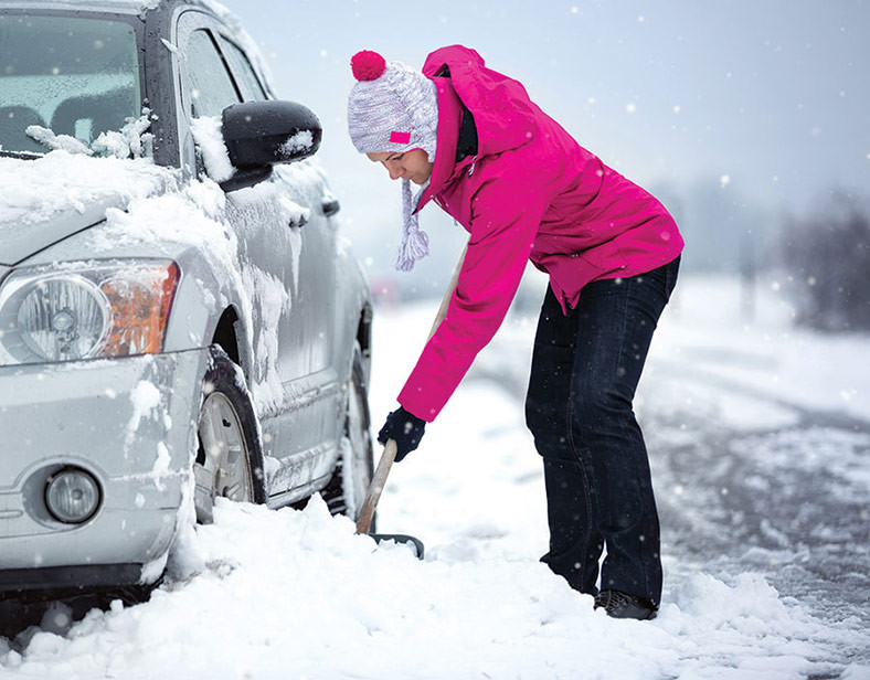 woman shovels snow to get car moving in winter