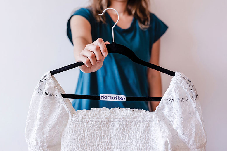 woman holds hanging clothes marked with Declutter sign