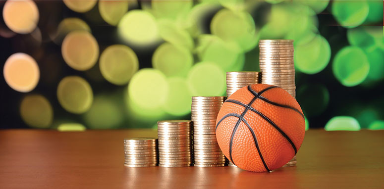 tiny basketball next to a stack of change financial planning in March