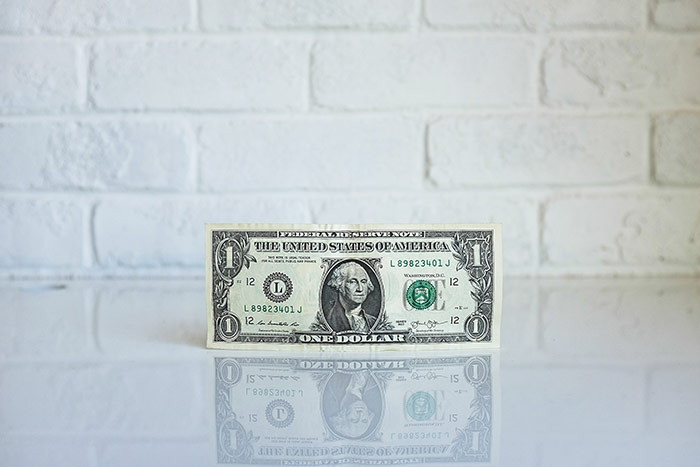 Picture of a dollar bill against a white brick wall