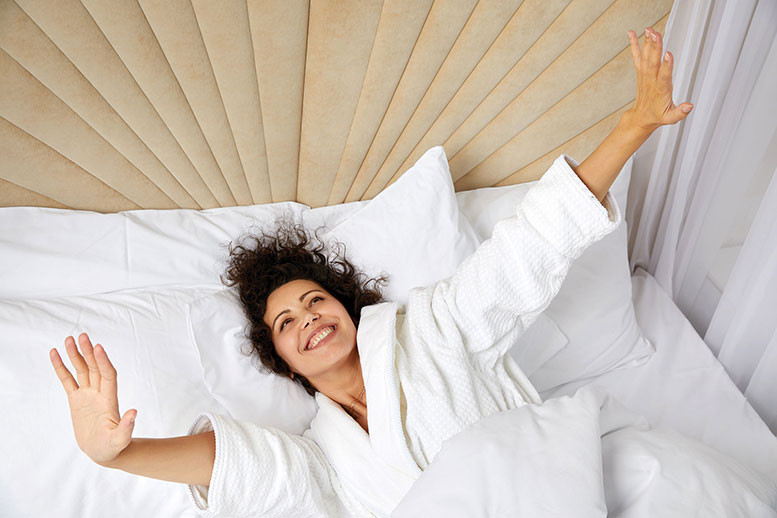 smiling woman stretches and wakes to a new day