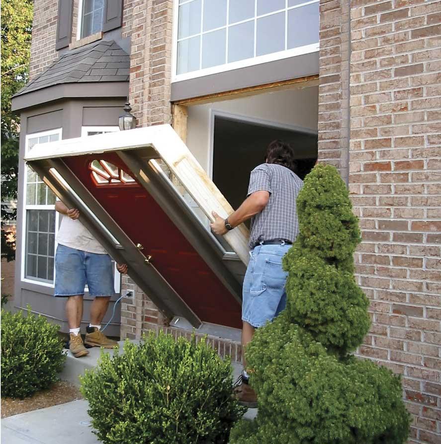 men installing entry door