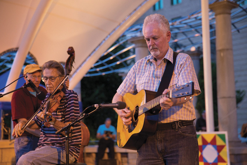 older couple playing music on stage