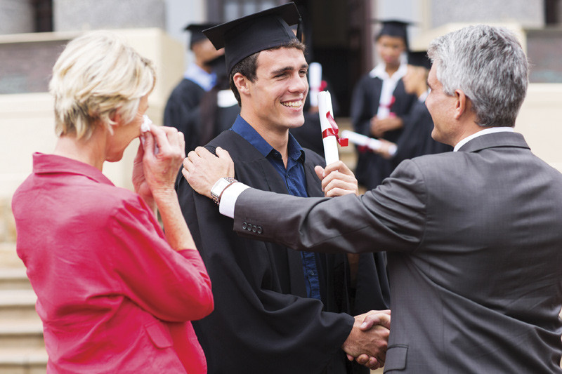 Older couple embrace college graduate