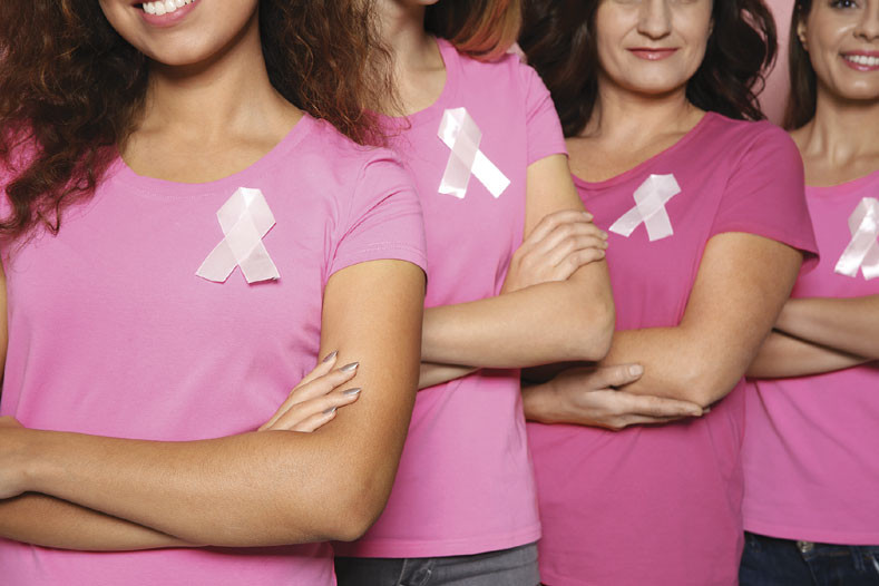 group of women wearing pink shirts and breast cancer ribbons